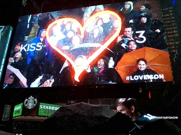 """If you stand in the right spot at Times Square, you'll see your face up on a billboard. I'm over there next to the """"3,"""" taking this picture with my cell phone."""