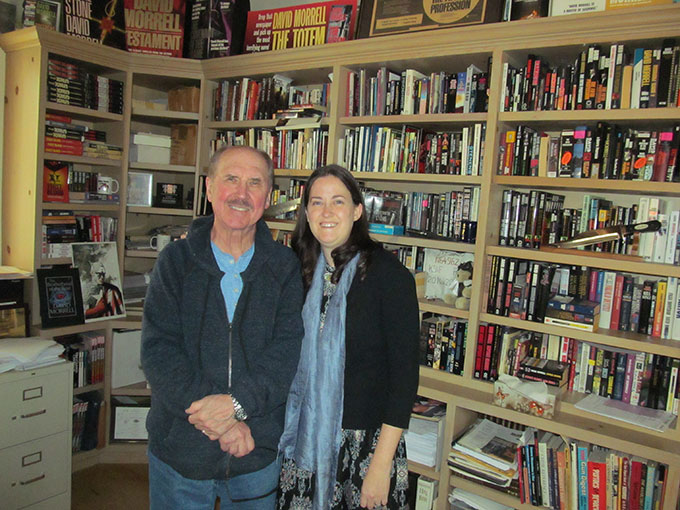 Deena with David Morrell in front of a bookcase of his novels.